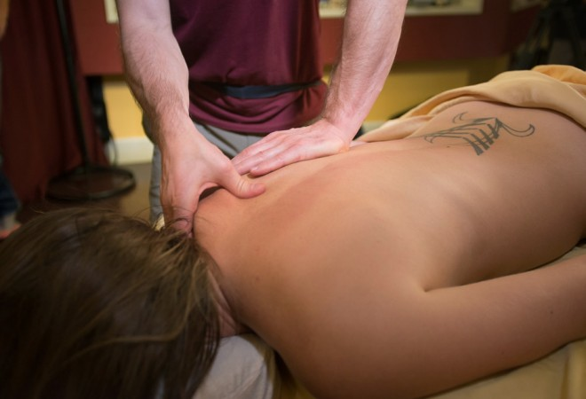 Image of a woman face down on a massage table. Felix massages her shoulder.
